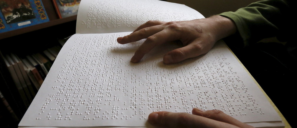 A visitor reads a book written in Braille at a specialized library for blind and partially sighted people in Krasnoyarsk, Siberia, Russia, March 15, 2016. REUTERS/Ilya Naymushin