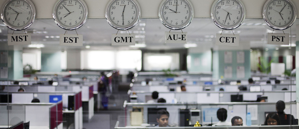Workers are pictured beneath clocks displaying time zones in various parts of the world at an outsourcing centre in Bangalore, February 29, 2012. India's IT industry, with Bangalore firms forming the largest component, is now worth an annual $100 billion and growing 14 percent per year, one of the few bright spots in an economy blighted by policy stagnation and political instability. Picture taken on February 29, 2012.  To match Insight INDIA-OUTSOURCING/  REUTERS/Vivek Prakash (INDIA - Tags: BUSINESS EMPLOYMENT SCIENCE TECHNOLOGY) - RTR30CVG