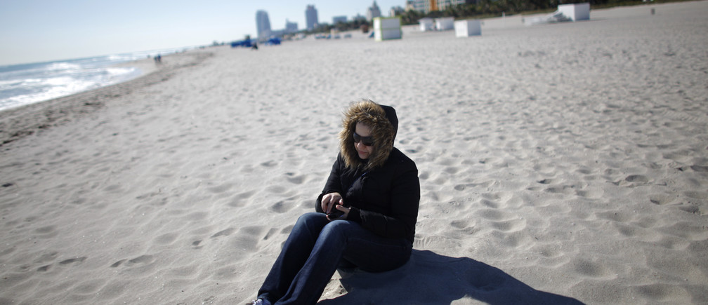 A tourist wearing a jacket sit at the beach in South Beach Miami, Florida January 11, 2010. Frigid temperatures below the freezing mark have not been seen in south Florida in 30 years. REUTERS/Carlos Barria (UNITED STATES - Tags: ENVIRONMENT SOCIETY TRAVEL) - GM1E61C02U901
