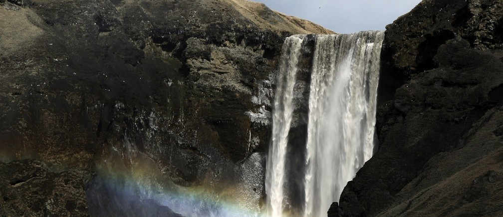 A woman stands near a waterfall that has been dirtied by ash that has accumulated from the ash plume of an erupting volcano near Eyjafjallajokull, Iceland April 18, 2010.