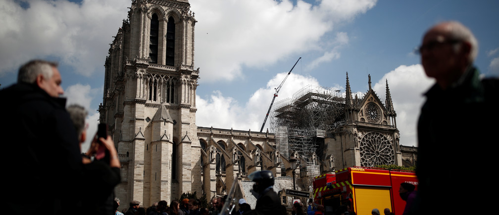 People look at Notre-Dame Cathedral two days after a massive fire devastated large parts of the gothic structure in Paris, France, April 17, 2019.   REUTERS/Benoit Tessier - RC19BF667BB0