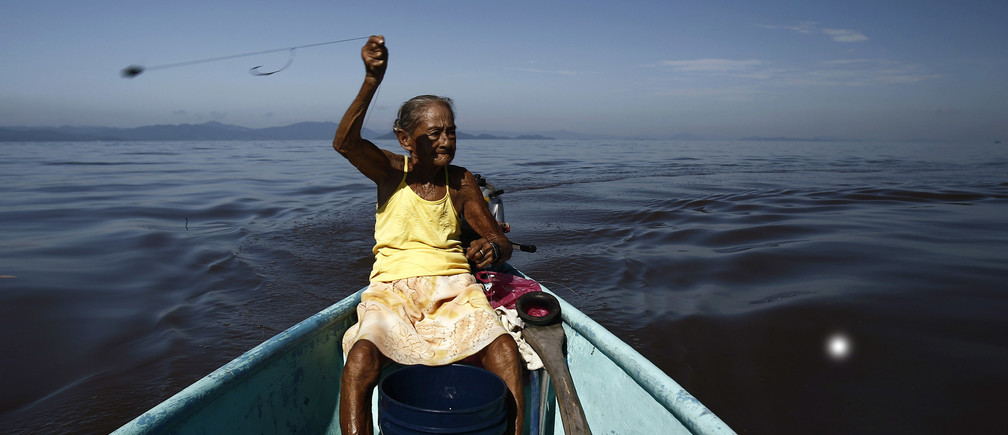Cecilia Villegas, 77, throws a fishing line along the sea of the Pacific coast of Cano Ciego Island near Puntarenas city October 3, 2012. Villegas leaves her home in Cano Ciego Island every morning to fish, which is her only means of survival. Fishing is the only source of income for the the thirty families in this small island.