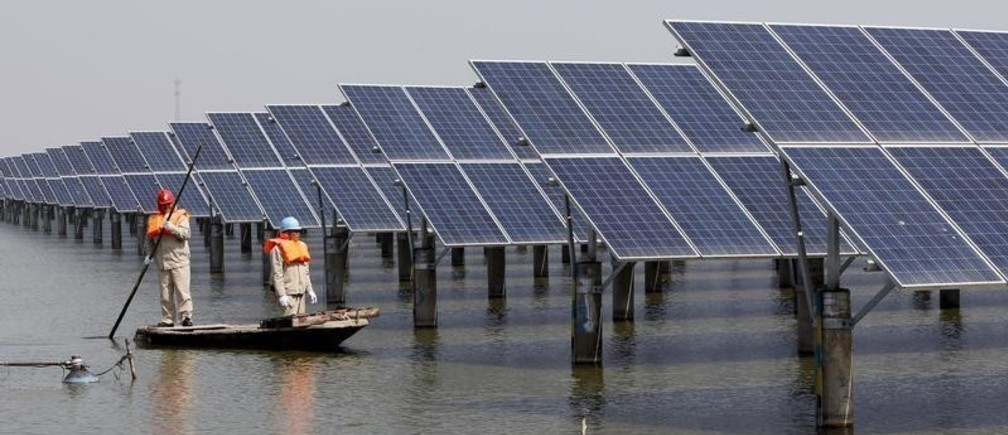 Employees row a boat as they examine solar panel boards at a pond in Lianyungang, Jiangsu Province, China, in this March 16, 2016 file photo. Global funds are cautiously venturing back into Chinese equities after prices collapsed to 4-1/2-year lows in February, taking advantage of cheaper valuations to buy stocks they believe will benefit from China's shift to a consumption-led economy. REUTERS/Stringer/Files    ATTENTION EDITORS - THIS PICTURE WAS PROVIDED BY A THIRD PARTY. THIS PICTURE IS DISTRIBUTED EXACTLY AS RECEIVED BY REUTERS, AS A SERVICE TO CLIENTS. CHINA OUT. NO COMMERCIAL OR EDITORIAL SALES IN CHINA  - GF10000366607