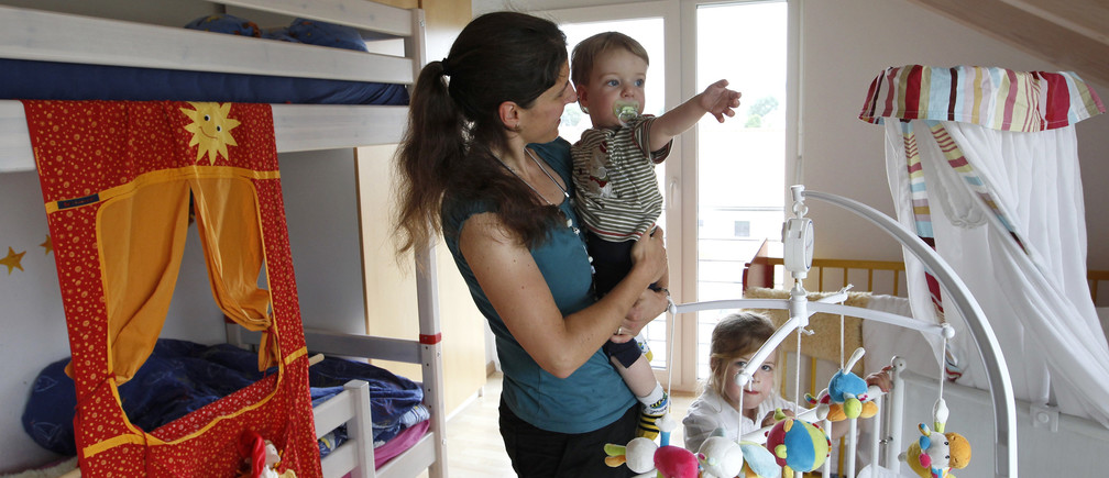 Claudia plays with her children Michael and Katharina at home in Durach, southern Germany June 20, 2012.