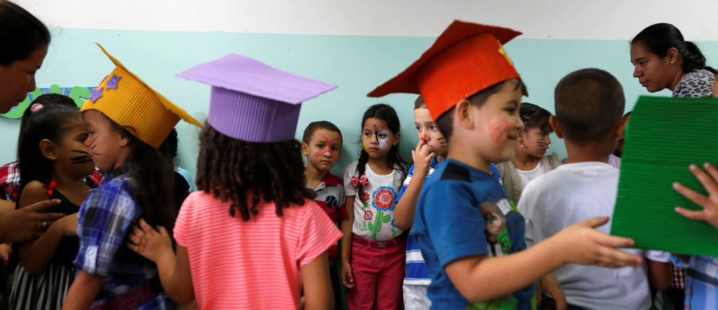 Students wearing handmade graduation hats take part in an activity for the end of the school year at the Padre Jose Maria Velaz school in Caracas, Venezuela July 12, 2016.