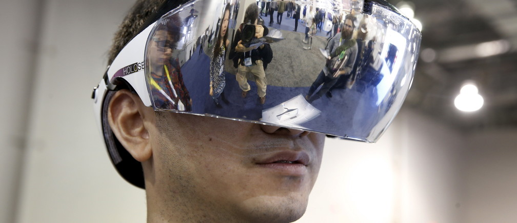 Kai Lee models a prototype Holoseer augmented-reality headset during the 2016 CES trade show in Las Vegas, Nevada January 8, 2016. The headset, with 100 degrees of view, is made by Caputer, a start-up company based in Shenzhen, China. REUTERS/Steve Marcus - GF20000088198
