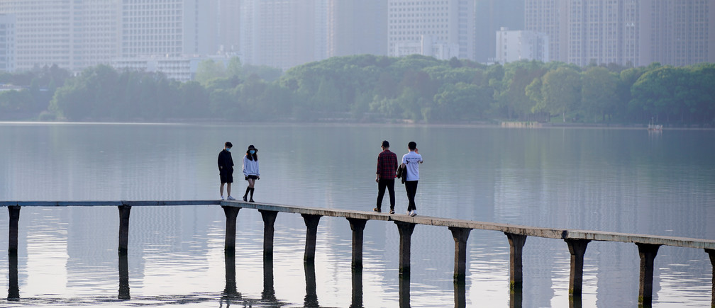 Des personnes portant des masques, marchant le long du lac de l'Est après la levée de la quarantaine à Wuhan, l'épicentre de l'épidémie de la nouvelle maladie coronavirus chinoise (COVID-19), à Wuhan, province de Hubei, en Chine, le 9 avril 2020.