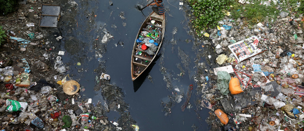 A man on a boat collects plastic materials from dirty water in Dhaka, Bangladesh, April 17, 2019. REUTERS/Mohammad Ponir Hossain - RC1395036C00