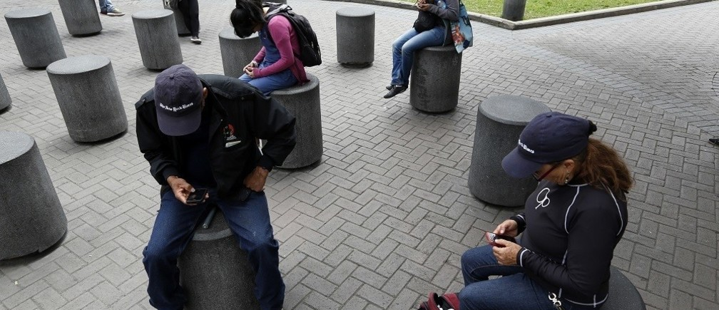 People use their smart phones as they sit at Kennedy park in Miraflores district in Lima, September 24, 2014.