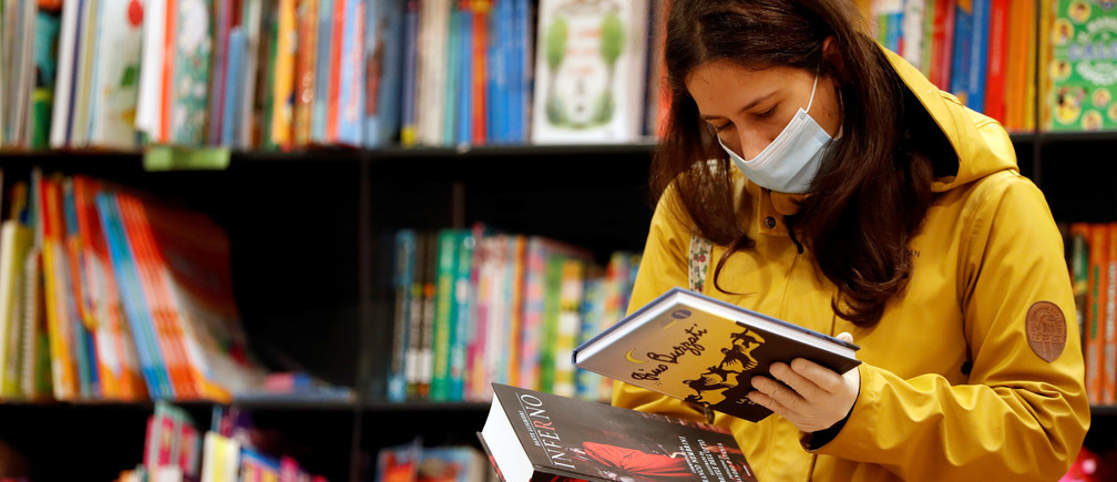 A customer wearing a protective face mask and gloves checks books at a newly opened bookstore, as only very few restrictions are relieved under the coronavirus disease (COVID-19) lockdown rules, in Rome, Italy April 20, 2020. REUTERS/Yara Nardi - RC298G9C3BB0