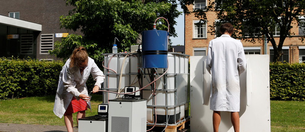 Belgian scientists Marjolein Vanoppen and Sebastiaan Derese (R) demonstrate the use of a machine that turns urine into drinkable water and fertilizer using solar energy, at the University of Ghent, Belgium, July 26, 2016. REUTERS/Francois Lenoir      TPX IMAGES OF THE DAY      - RTSJQFW