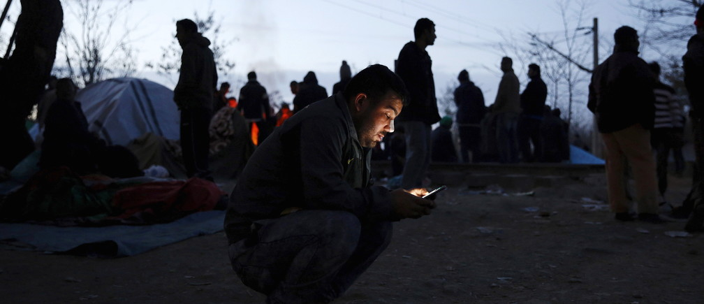 A migrant checks his smart phone as he waits at the Greek-Macedonian border in 2015.