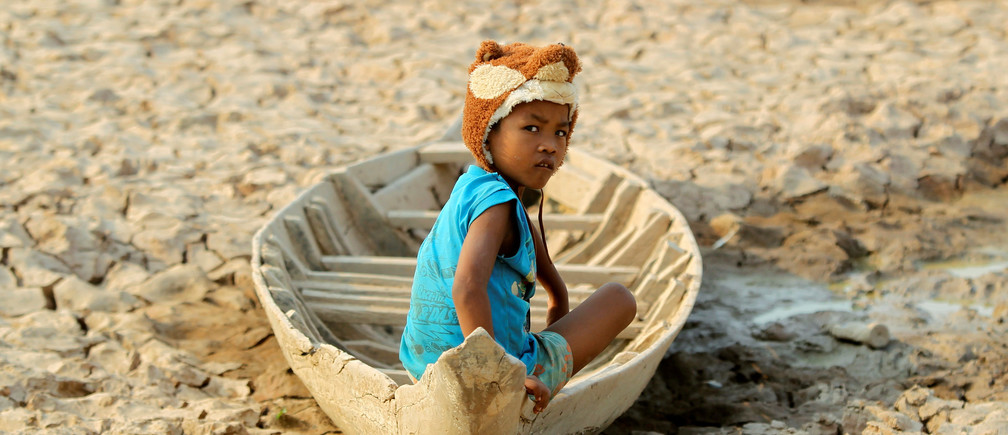 A girl sits on her boat at a Bak Angrout dried up pond at the drought-hit Kandal province in Cambodia May 13, 2016.
