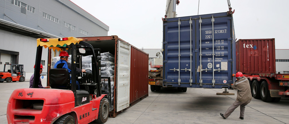 Men work on unloading the rubber imported from Belt and Road Initiative (BRI) countries at a bonded logistics centre in Nantong, Jiangsu province, China, May 2019.
