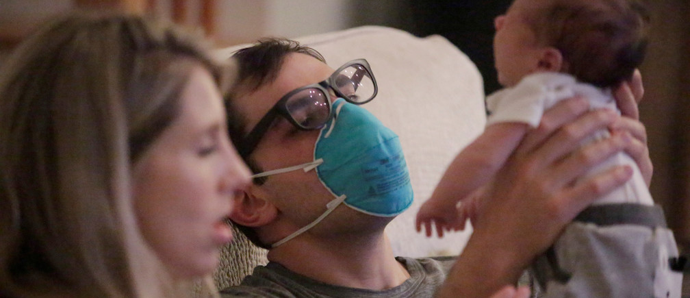 Emergency medicine physician Thomas Krajewski wears a mask as he holds his baby Cal with his wife Genevieve after finishing his shift amid an outbreak of coronavirus disease (COVID-19) in New Orleans, Louisiana, U.S., March 27, 2020. Picture taken March 27, 2020.  REUTERS/Kathleen Flynn     TPX IMAGES OF THE DAY - RC24UF9W8LKC