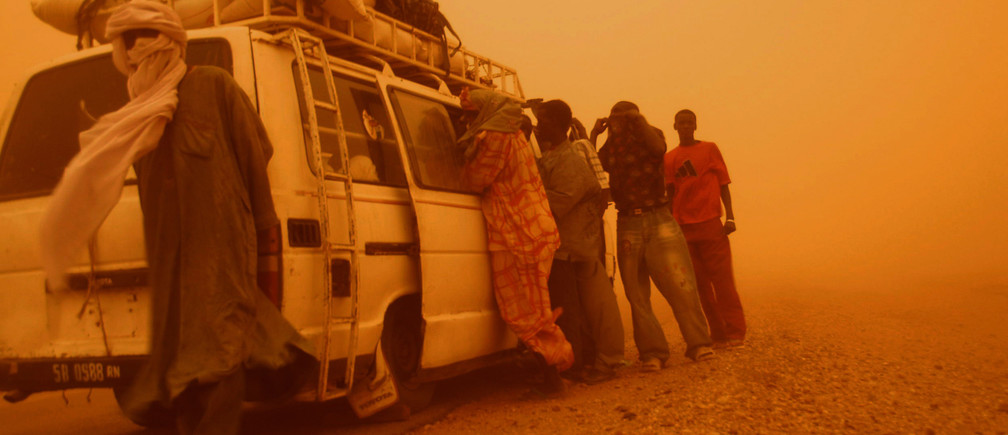 "December 19, 2006Passengers stand outside their taxi during a sandstorm raised by the annual dry ""Harmattan wind"", along the road that links the historic centre of Agadez with Arlit, in the Agadez region"