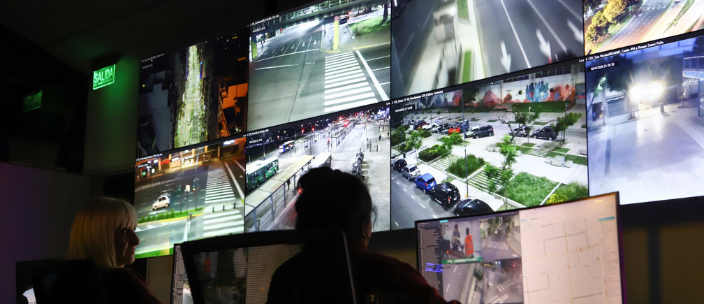 Los oficiales de policía monitorean el tráfico en las calles a partir de las imágenes de las cámaras de vigilancia durante el encierro, Argentina