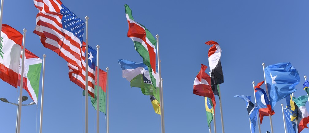 Flags of various nations against a blue sky.