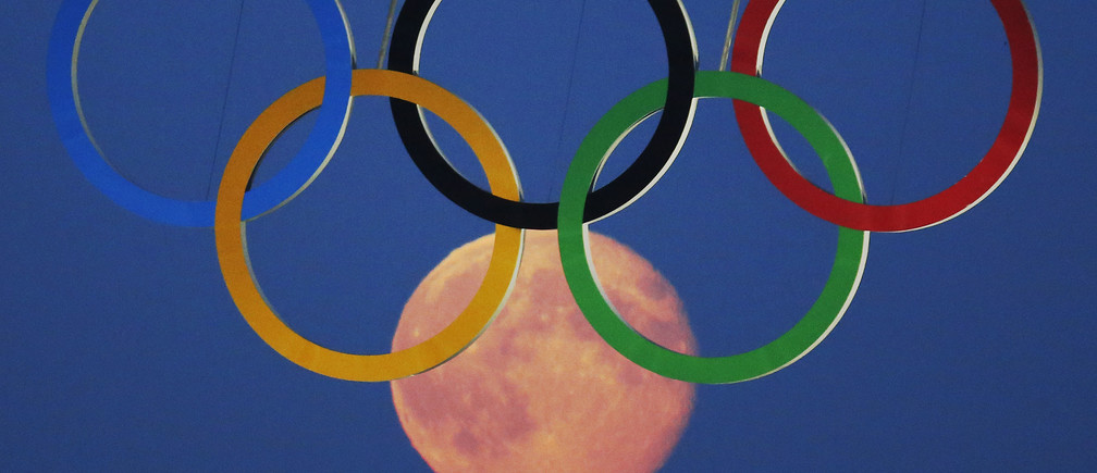 The full moon rises through the Olympic Rings hanging beneath Tower Bridge during the London 2012 Olympic Games August 3, 2012.  REUTERS/Luke MacGregor  (BRITAIN - Tags: SPORT OLYMPICS CITYSPACE TPX IMAGES OF THE DAY ENVIRONMENT) - RTR362IE
