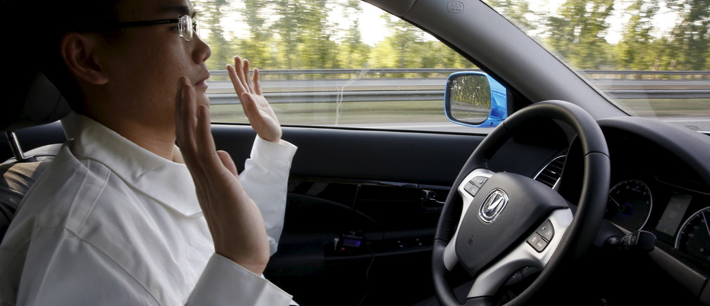 Li Zengwen, a development engineer at Changan Automobile, lifts his hands off the steering wheel as the car is on self-driving mode during a test drive on a highway in Beijing, China, April 16, 2016. REUTERS/Kim Kyung-Hoon - RTX2BA9H