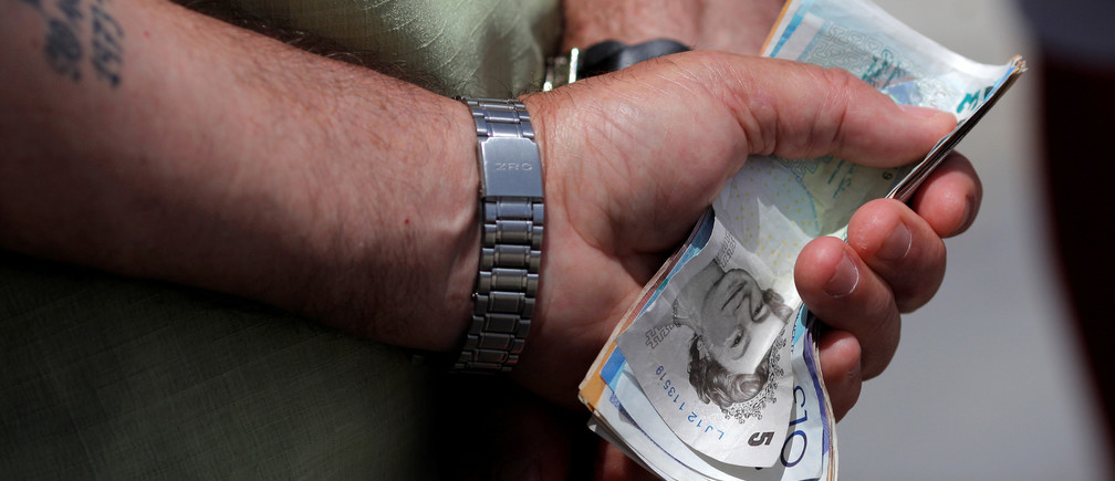 A man holds various English Pound notes as he waits in line to exchange it for Euros notes outside a money exchange office in the British overseas territory of Gibraltar, historically claimed by Spain, June 24, 2016, after Britain voted to leave the European Union in the EU BREXIT referendum. REUTERS/Jon Nazca - S1AETLTXIYAA