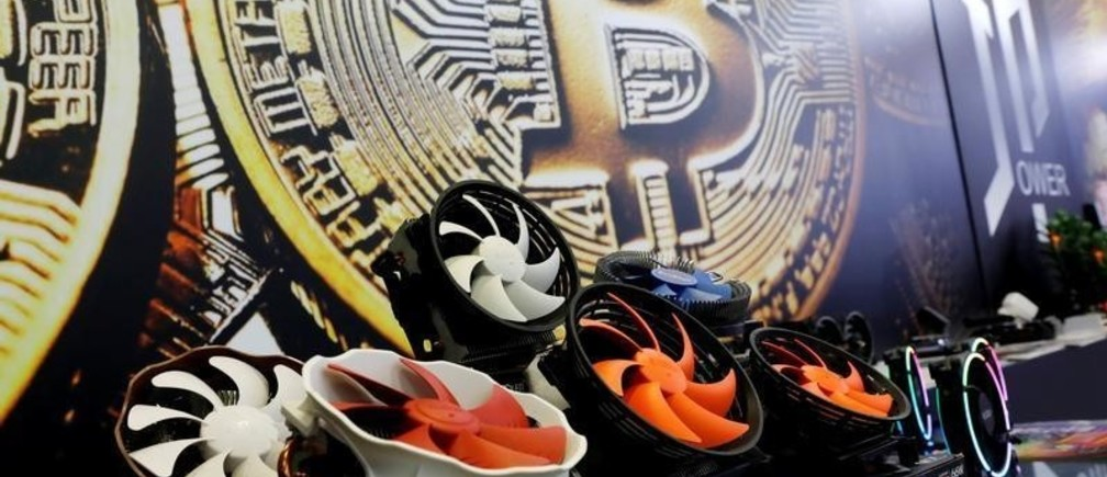 Cryptocurrency mining computer fans are seen in front of bitcoin logo during the annual Computex computer exhibition in Taipei, Taiwan June 5, 2018. REUTERS/Tyrone Siu - RC1951242020