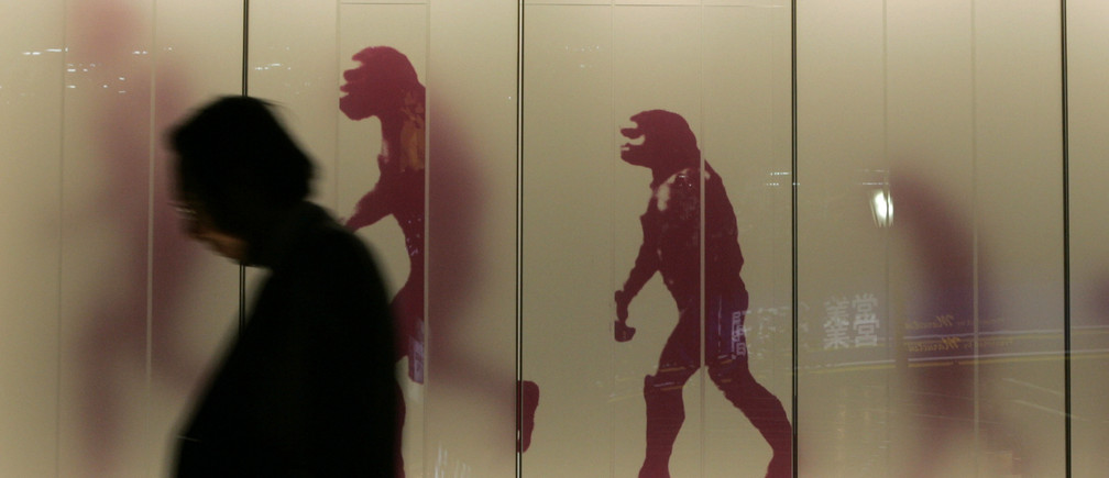 A man walks past a sign showing the evolution of man in a business district in downtown Tokyo November 17, 2008. Japan slid into its first recession in seven years in the third quarter as exports crumbled, and some analysts said an escalation in the global financial crisis may have put the economy on course for its longest ever contraction. REUTERS/Michael Caronna (JAPAN) - RTXAOFA