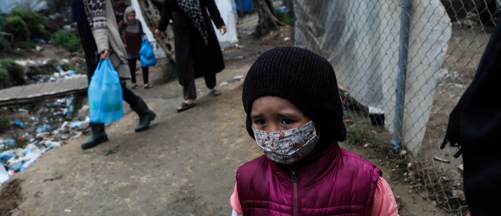 A girl wears a protective face mask at a makeshift camp for refugees and migrants next to the Moria camp, during a nationwide lockdown to contain the spread of the coronavirus disease (COVID-19), on the island of Lesbos, Greece April 02, 2020. REUTERS/Elias Marcou - RC2IWF9Q4OTQ