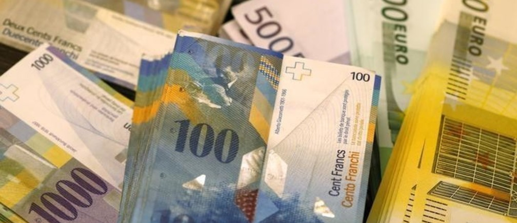 """Swiss Franc and Euro banknotes of several values lie on a table in a Swiss bank in Bern November 25, 2014. The """"Save our Swiss gold"""" proposal, spearheaded by the right-wing Swiss People's Party (SVP), aims to ban the central bank from offloading its reserves and oblige it to hold at least 20 percent of its assets in gold. The referendum is scheduled for November 30. The SVP argues it would secure a stable Swiss franc.  Picture taken November 25, 2014.  REUTERS/Ruben Sprich (SWITZERLAND  - Tags: POLITICS BUSINESS)"""