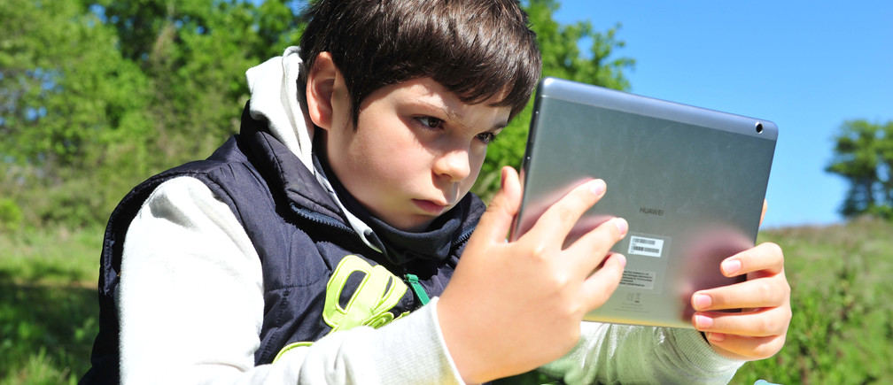 Giulio Giovannini, 12, with a tablet, a small camping table and a chair, studies on the top of a hill where he is able to access the Internet so he can participate in online lessons while schools remain closed due to the spread of the disease from coronavirus (COVID-19), in Scansano, Italy, April 15, 2020. REUTERS/Jennifer Lorenzini - RC205G91UR4B