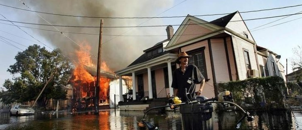A man stands in flood waters as fire burns down a home in the seventh ward of New Orleans in the aftermath of Hurricane Katrina September 6, 2005. The toxic brew of chemicals and human waste in the New Orleans floodwaters will have to be pumped into the Mississippi River or Lake Pontchartrain, raising the specter of an environmental disaster on the heels of Hurricane Katrina, experts say. Pictures of the Year 2005 REUTERS/Shannon Stapleton  SS/CN