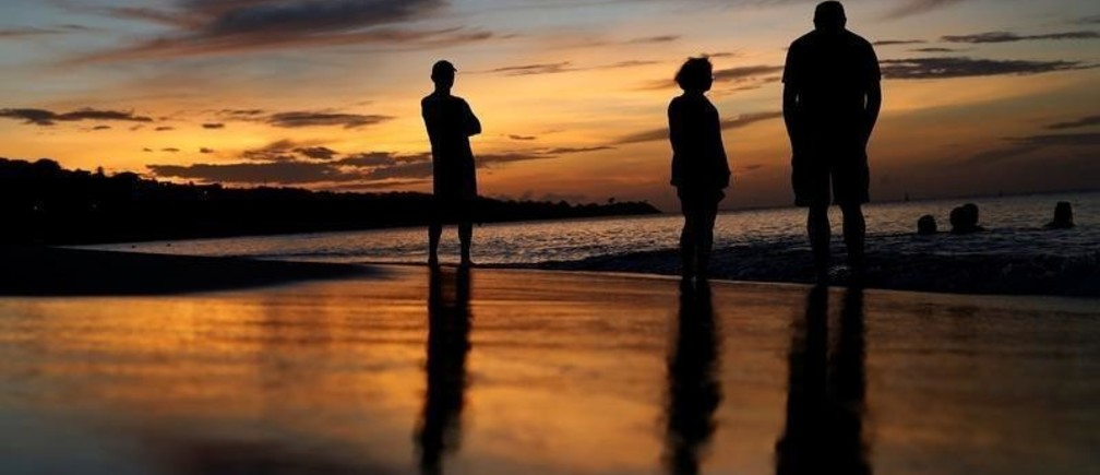 People stand and watch the sunset on Grand Anse Beach in St. George's, Grenada, November 27,  2016. REUTERS/Carlo Allegri - RC1A4AA60E00