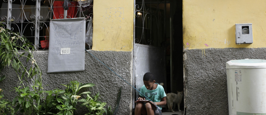 A boy plays on his tablet outside his house at the Mare slums complex in Rio de Janeiro March 25, 2014. Brazil will deploy federal troops to Rio de Janeiro to help quell a surge in violent crime following attacks by drug traffickers on police posts in three slums on the north side of the city, government officials said on Friday. Less than three months before Rio welcomes tens of thousands of foreign soccer fans for the World Cup, the attacks cast new doubts on government efforts to expel gangs from slums using a strong police presence. The city will host the Olympics in 2016. REUTERS/Ricardo Moraes (BRAZIL - Tags: CRIME LAW) - RTR3IKKO