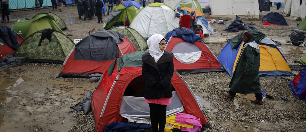 A migrant woman stands outside a tent at a makeshift camp on the Greek-Macedonian border near the village of Idomeni, Greece March 10, 2016.