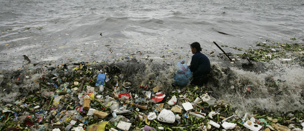 A man collects recyclable plastic materials, washed ashore by waves.