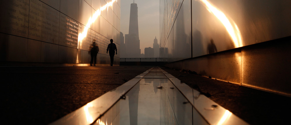 A man walks through the 9/11 Empty Sky memorial at sunrise across from New York's Lower Manhattan and One World Trade Center in Liberty State Park in Jersey City, New Jersey, September 11, 2013