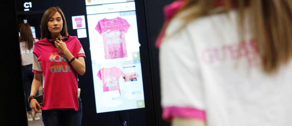 A model demonstrates Alibaba's FashionAI technology, with the chosen item's details being displayed on the mirror, at a pop-up store in partnership with fashion brand GUESS, on the sidelines of the Artificial Intelligence on Fashion and Textile Conference at the Hong Kong Polytechnic University in Hong Kong, China July 3, 2018. Picture taken July 3, 2018. REUTERS/Bobby Yip - RC189100E300