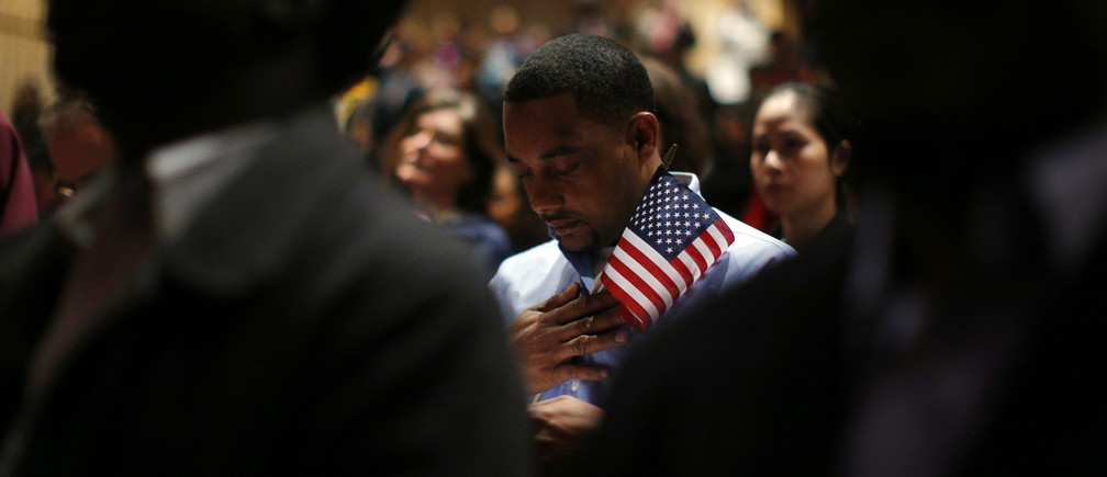 Immigrants stand for the invocation during a naturalization ceremony to become new U.S. citizens at Boston College in Chestnut Hill, Massachusetts March 21, 2013.