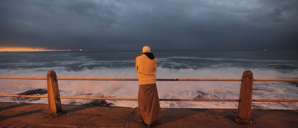 A Cape Town Muslim awaits the sighting of the crescent moon marking Eid al-Fitr, the end of Ramadan, the holiest month in the Islamic calendar, along the city's Sea Point beachfront, September 9, 2010.   REUTERS/Mike Hutchings  (SOUTH AFRICA - Tags: RELIGION SOCIETY) - GM1E69A0FEG01