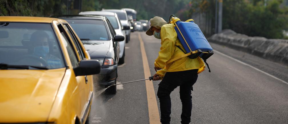 Un voluntario higieniza los automóviles antes de que entren en su municipio como medida preventiva durante una cuarentena en todo el país, ya que el gobierno toma medidas cada vez más estrictas para evitar una posible propagación de la enfermedad coronavírica (COVID-19), en Santo Tomás (El Salvador) el 28 de abril de 2020.