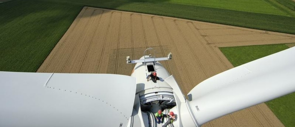 Employees work on the top of an E-70 wind turbine manufactured by German company Enercon for La Compagnie du Vent (GDF SUEZ Group) during its installation at a wind farm in Meneslies, Picardie region, July 31, 2014. France announced in July a package of tax breaks and low-cost loans to improve insulation in buildings and boost investment in renewable energy, which is supposed to provide 40 percent of the country's electricity by 2030. Picture taken July 31, 2014.  REUTERS/Benoit Tessier   (FRANCE - Tags: ENERGY BUSINESS CONSTRUCTION ENVIRONMENT) - PM1EA841DXC01