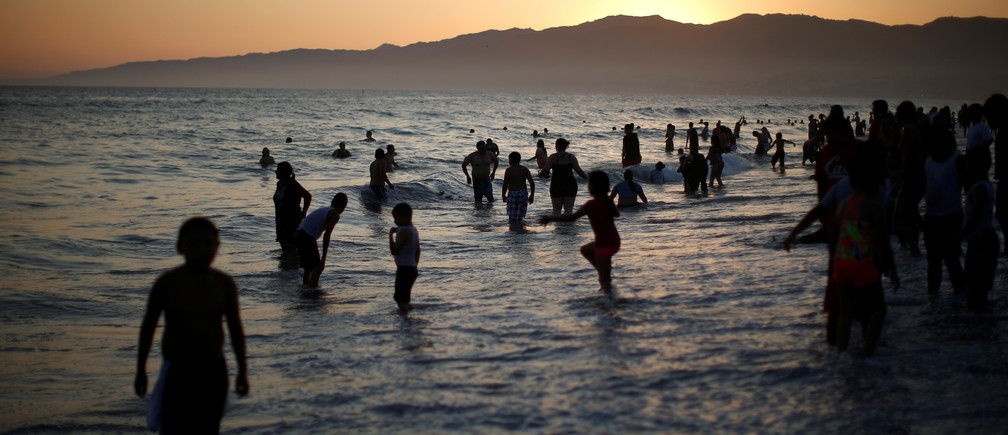 People cool off in the Pacific Ocean during a record-setting heat wave across the U.S. Southwest, on the summer solstice in Santa Monica, California, U.S. June 20, 2016.