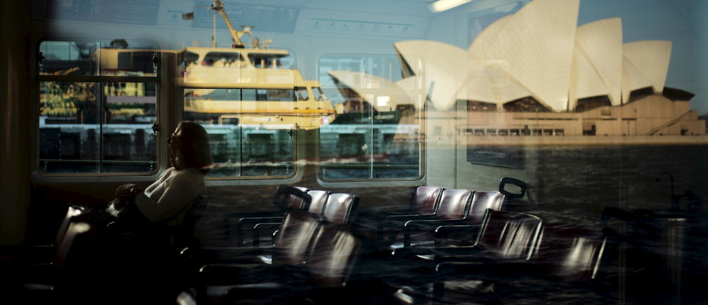 A commuter yawns on a Circular Quay-bound inner-harbour ferry as the Manly Ferry 'Freshwater' is reflected while it passes by the Sydney Opera House, November 24, 2015.