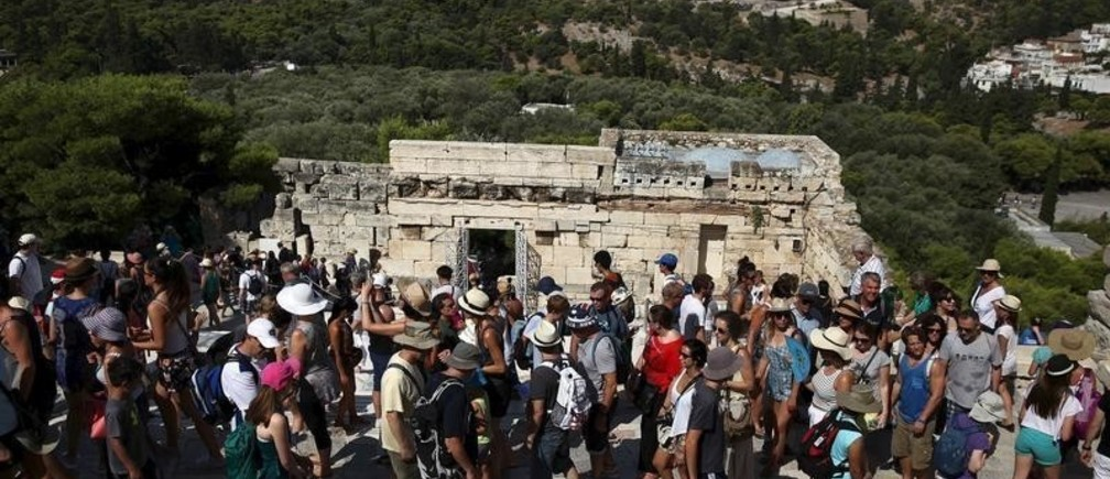 Tourists make their way in front of the Propylaia at the archaeological site of the Acropolis hill in Athens, Greece August 4, 2015. Hard numbers for tourist arrivals in Greece are difficult to come by because it is only just high season, but there are signs.Aegean Airlines, Greece's largest carrier, says passenger traffic was up 19 percent in July compared with the same month last year. Picture taken August 4, 2015.