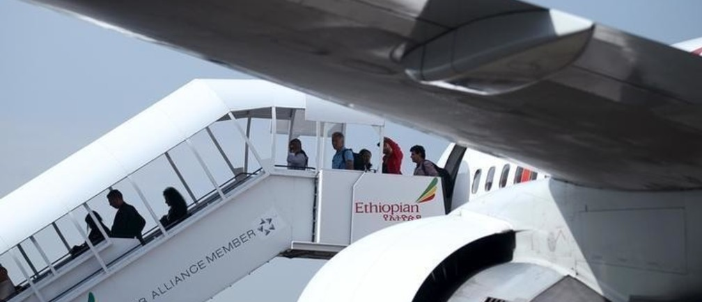 Passengers disembark from an Ethiopian Airlines plane at the Bole International Airport in Ethiopia's capital Addis Ababa August 21, 2015. Ethiopian Airlines is powering ahead with a plan to expand its fleet and route network after exceeding its profit target for the 2014/15 year, its chief executive said in an interview. To match Interview ETHIOPIAN-AIRLINES/REUTERS/Tiksa Negeri