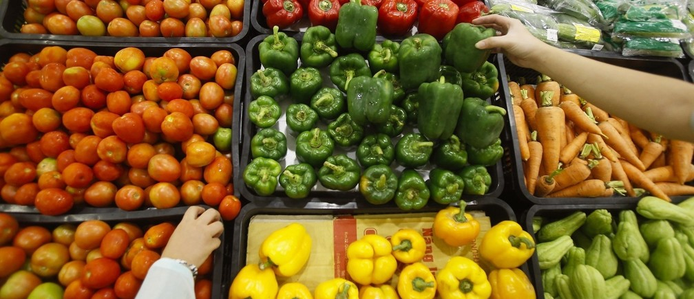 Customers select vegetables at a supermarket in Hanoi