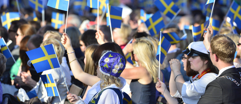 People in the audience wave Swedish flags during the traditional National Day celebrations with the royal family at Skansen in Stockholm June 6, 2013. REUTERS/Henrik Montgomery/Scanpix