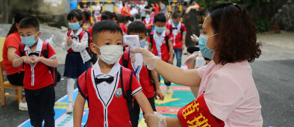 A staff member takes body temperature measurement of schoolchildren at a kindergarten that has resumed operation following the coronavirus disease (COVID-19) outbreak, in Yongzhou, Hunan province, China May 11, 2020. Picture taken May 11, 2020. China Daily via REUTERS  ATTENTION EDITORS - THIS IMAGE WAS PROVIDED BY A THIRD PARTY. CHINA OUT. - RC2SMG9TU6GK