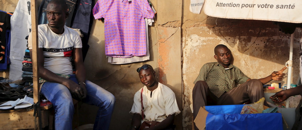 Vendors sit against a wall outside a bus station in Ouagadougou, Burkina Faso.