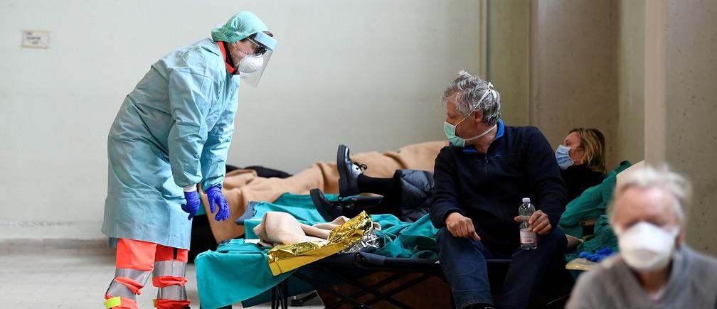 El personal médico que usa máscaras faciales de protección ayuda a los pacientes dentro del hospital civil Spedali en Brescia, Italia, el 13 de marzo de 2020.